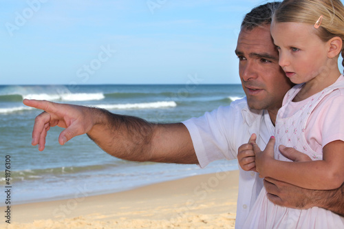 Father and daughter pointing at something on the beach