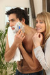 Young man shaving with his girlfriend watching