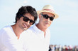 Two men in white tops and sunglasses