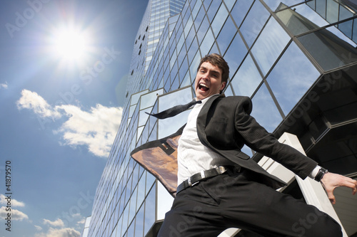 Businessman and success jumping for joy before the office