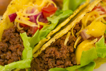 Close up of Mexican minced beef tacos with salsa and cheese.