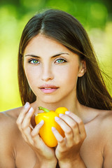 woman with bare shoulders holding yellow pepper