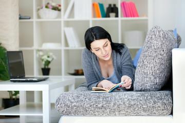 Women Reading a Book on Sofa