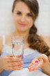 Closeup on pills and glass of water in hand of happy woman