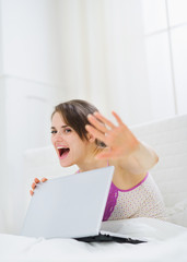 Woman hiding what she doing on laptop