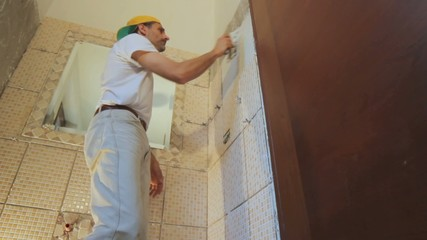 man installing tiles in a bathroom