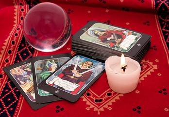 Tarot cards and crystal ball on red cloth