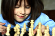Little girl plays chess.