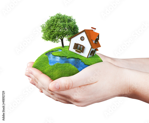 Hands holding house on clear green meadow, tree and river
