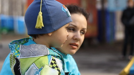 Close up of a young mother and child, talking in the park