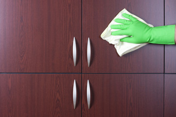 cleaner hand polishing the door of closet
