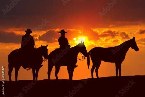 cowboys and horses under sunset