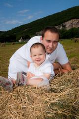 jeune papa et son fils dans la prairie