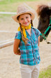 Lovely cowgirl and pony on a ranch