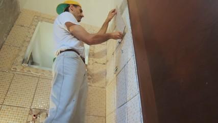 tiler installing tiles in a bathroom