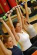 Mujeres jóvenes haciendo ejercicio en un gimnasio.