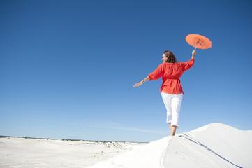 Happy mature woman balancing on sand dune