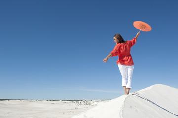 Beautiful woman balancing on sand dune rim