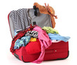 Open red suitcase with clothing isolated on white