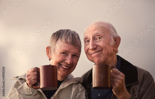 Smiling Senior Couple Toasting with Mugs