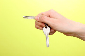 Keys in hand on green background