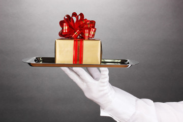 Hand in glove holding silver tray with giftbox