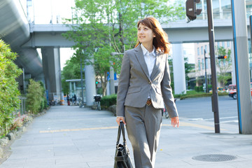 Beautiful business woman walking outside her office