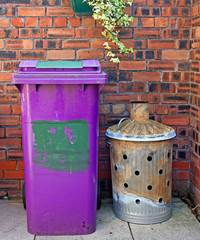 Wheelie bin and garden incinerator against brick wall