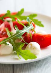 Caprese salad with arugula leaves