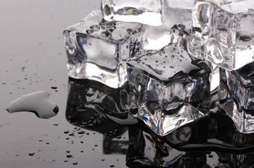 Melting ice cubes on black background
