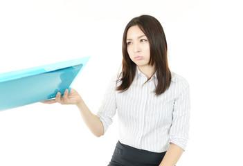 書類を持ち不満そうな表情のオフィスレディー