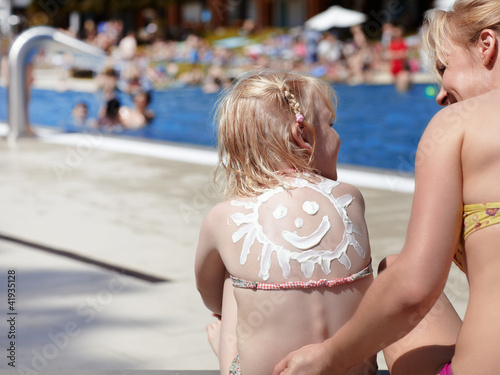 Mother and child with sunblocker on the back in open-air bath