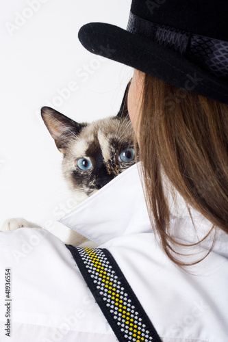 the cat looks out from behind the girl in the hat