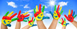 Many coloured hands of children in front of blue sky