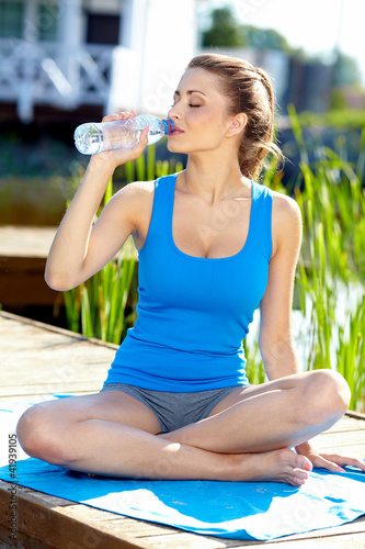 portrait of young woman drinking water against a plants backgrou