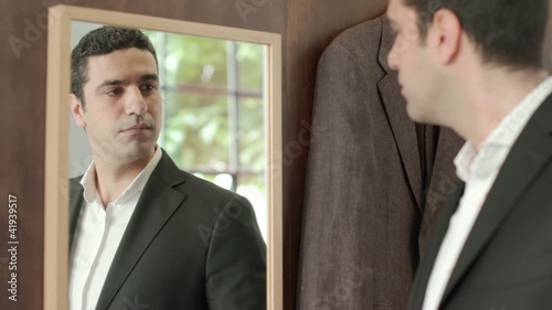 Adult man dressing up with suit and looking at mirror