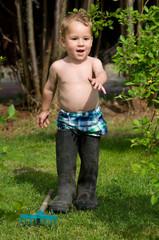 Kleiner Junge wandert mit Papas Gummistiefel