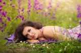 Beautiful young woman in purple flowers outdoors