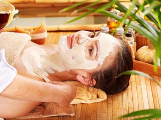 Woman having clay facial and body mask.