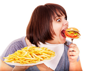 Overweight woman eating hamburger.