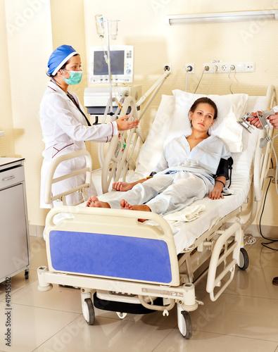 Doctor treats patient with defibrillator.