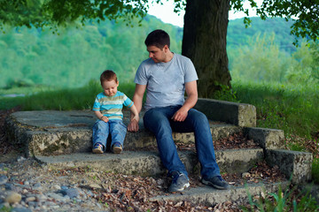 father and son sitting on stairs under an old tree. family ties