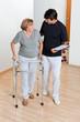 Trainer Looking At Senior Woman Using Walker