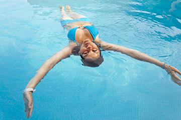 mujer joven nadando en piscina