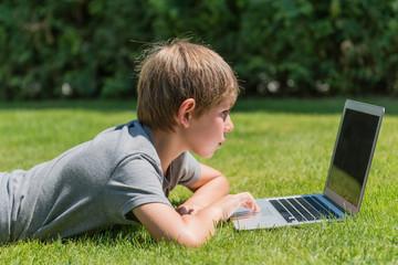 Junge mit Notebook auf einer Wiese