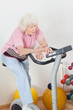 Tired Senior Woman Exercising On Bike