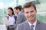 Handsome businessman standing in front of group of people