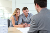 Couple in real-estate agency talking to construction planner