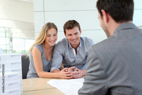 Couple in real-estate agency talking to construction planner - 41956308