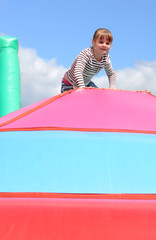 Happy child girl on the inflatable playground's top
